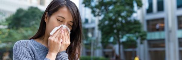 vrouw snuit neus in zakdoek bij hooikoorts